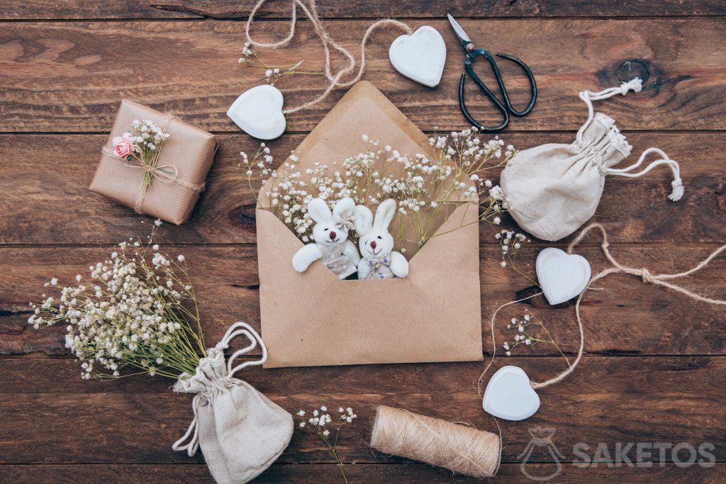 Linnen tas met gips, pluche konijntjes in een envelop en een geschenk verpakt in grijs papier