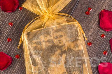 Elegant, goudkleurig organzazakje als verpakking voor een foto van de pasgehuwden.