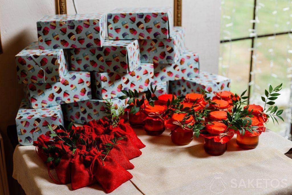 Geschenkdozen verpakt in gekleurd papier, jute rode zakken en potten met conserven