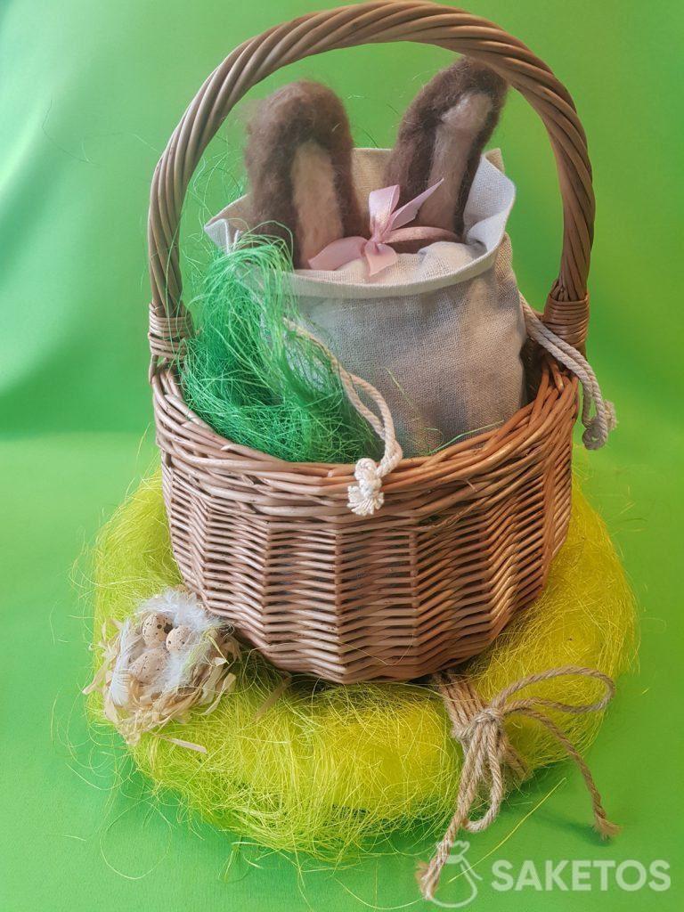 Mandje met een linnen zakje waaruit de kamgaren oren van een vilten konijntje steken