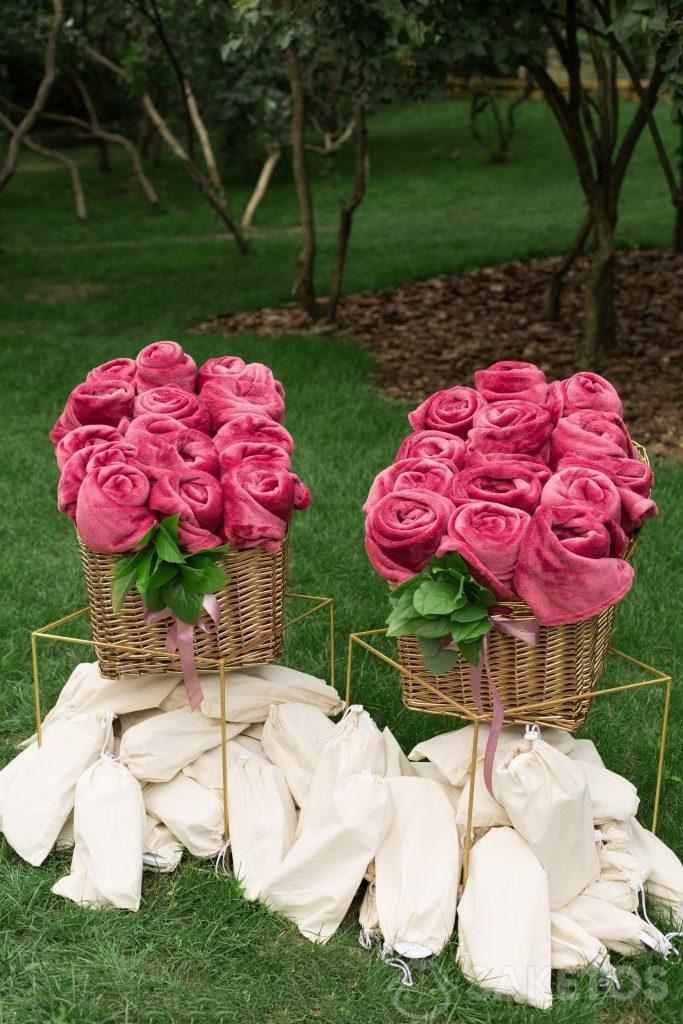 Versierde opgerolde dekens en slippers in linnen zakken voorbereid voor bruiloftsgasten