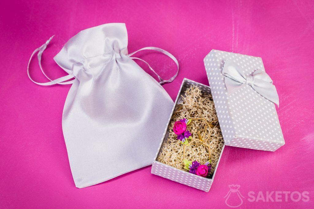 Zilveren satijnen tas als elegante verpakking voor een kartonnen juwelendoos met oorbellen.
