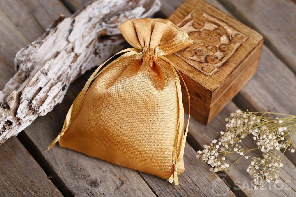 Goudkleurig zakje van satijn en een klein houten kistje voor souvenirs