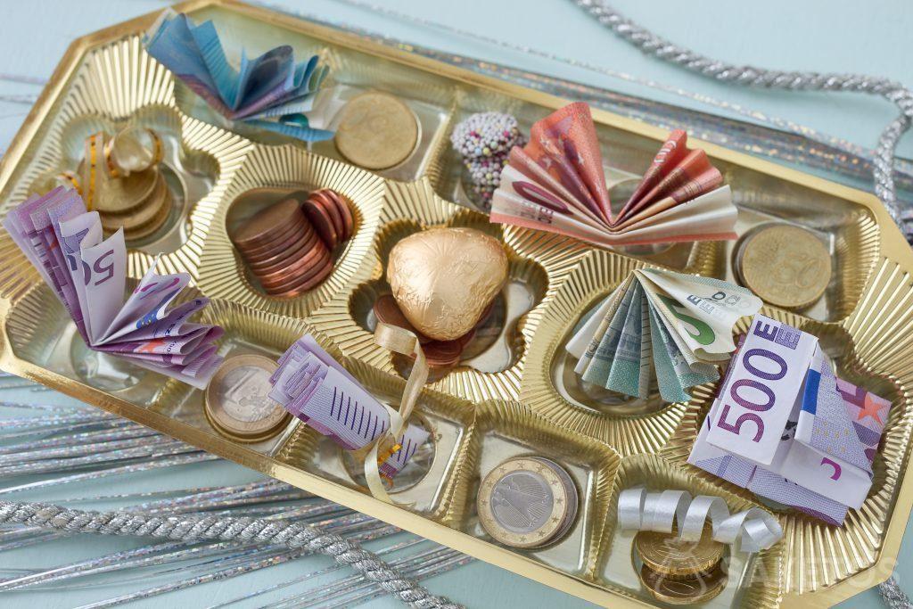 Bankbiljetten of geldmunten kunnen in de doos met pralines en tussen de pralines geplaatst worden.
