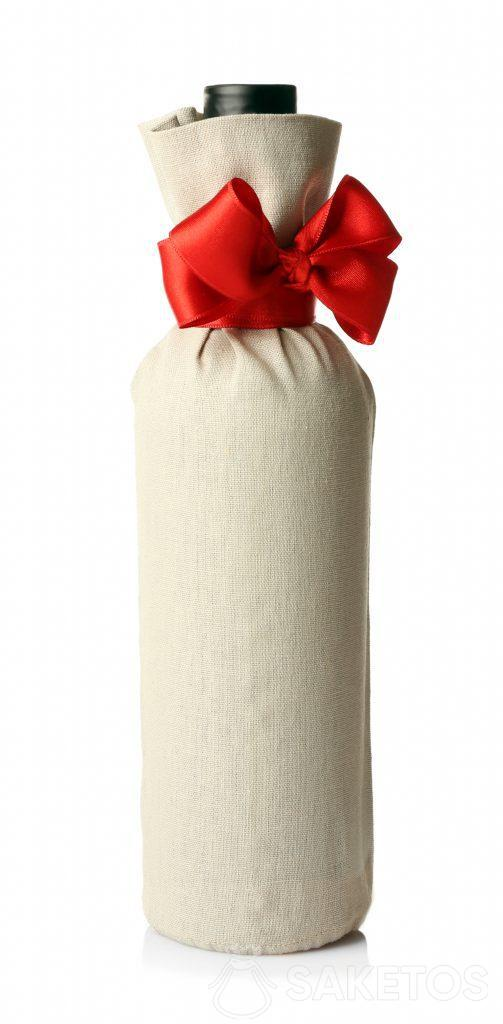 Een fles alcohol, verpakt als cadeau in een linnen zakje en met een rode strik