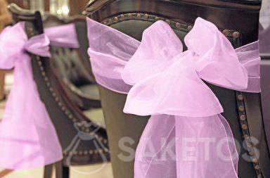 Een decoratieve organza strik gebonden aan de rugleuning van de stoel