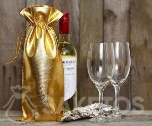 Een fles wijn gewikkeld in een gouden metalen zak