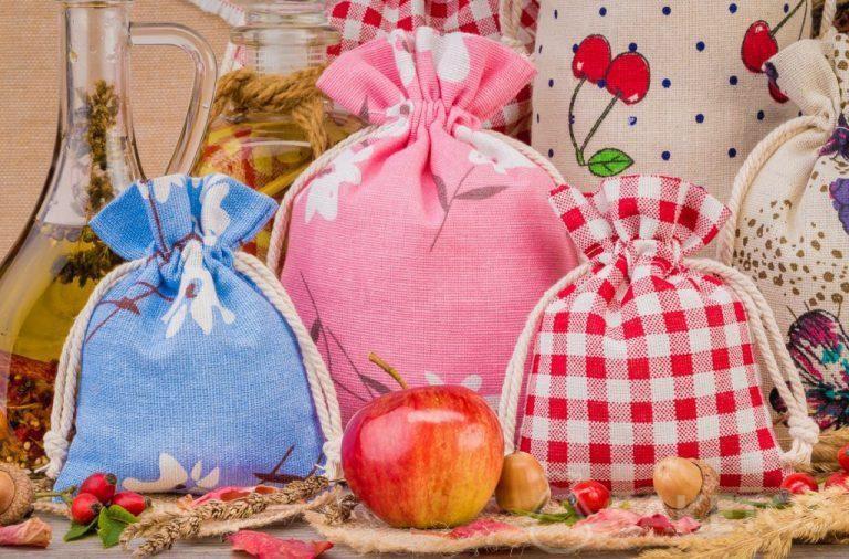 Linnen zakjes met gekleurde opschriften voor interieur decoraties.Een zakje van organza is een elegante verpakking voor een kaars.