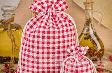 Modieuze rood geruite linnen zakjes zijn een geweldige decoratie voor Uw keukenwerkblad of plank.
