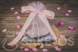 Een zakje van linnen toegebonden met een versierende strik van een lint met een decoratief hangertje