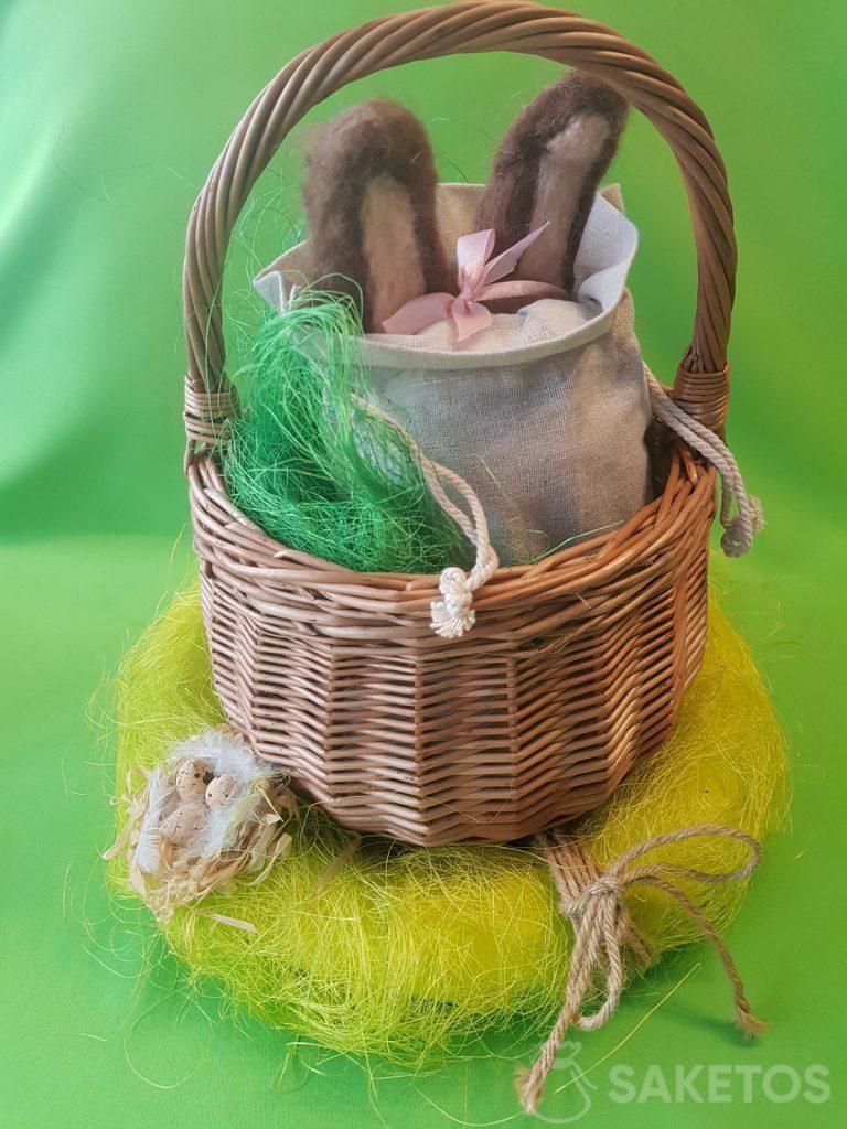 Een mandje met een linnen zakje waaruit de oren van een vilten konijntje uitsteken.