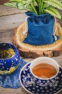 4.Een keramiek kopje met thee en een jeanszakje als bloempot